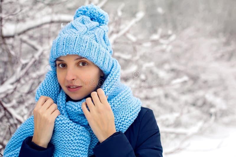 Χαμογελώντας κορίτσι σε ένα πλεκτό μπλε μαντίλι, και στάσεις ΚΑΠ στοκ εικόνες
