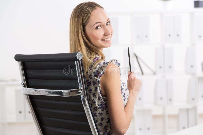 Χαμογελώντας κορίτσι στην sviwel-καρέκλα στοκ φωτογραφία