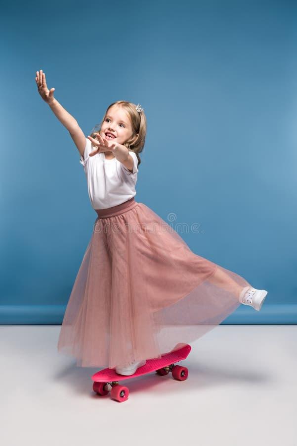 Χαμογελώντας κορίτσι στη ρόδινη φούστα που στέκεται skateboard και την κατοχή της διασκέδασης στοκ φωτογραφία