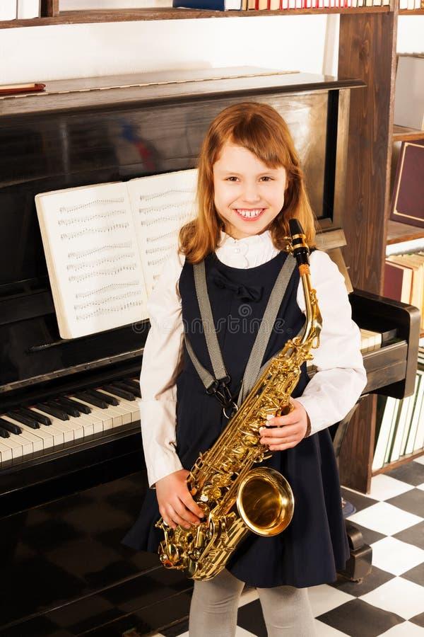 Χαμογελώντας κορίτσι στη σχολική στολή με το saxophone alto στοκ εικόνα με δικαίωμα ελεύθερης χρήσης