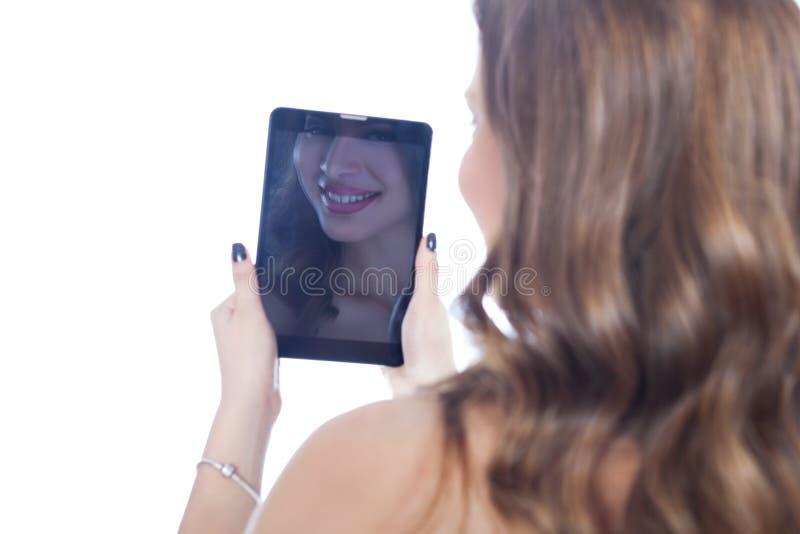 Χαμογελώντας κορίτσι στον υπολογιστή ταμπλετών στοκ εικόνες