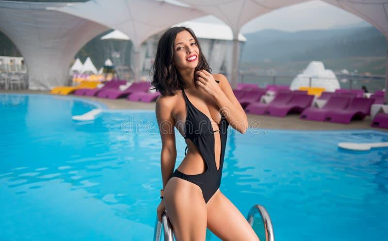 Χαμογελώντας κορίτσι brunette στο μαύρο μαγιό με το εύμορφο σώμα κοντά στην πισίνα στο θέρετρο βουνών στοκ εικόνα με δικαίωμα ελεύθερης χρήσης