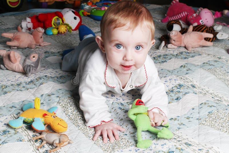 Χαμογελώντας κοριτσάκι στο πάτωμα με τα παιχνίδια στοκ φωτογραφία με δικαίωμα ελεύθερης χρήσης