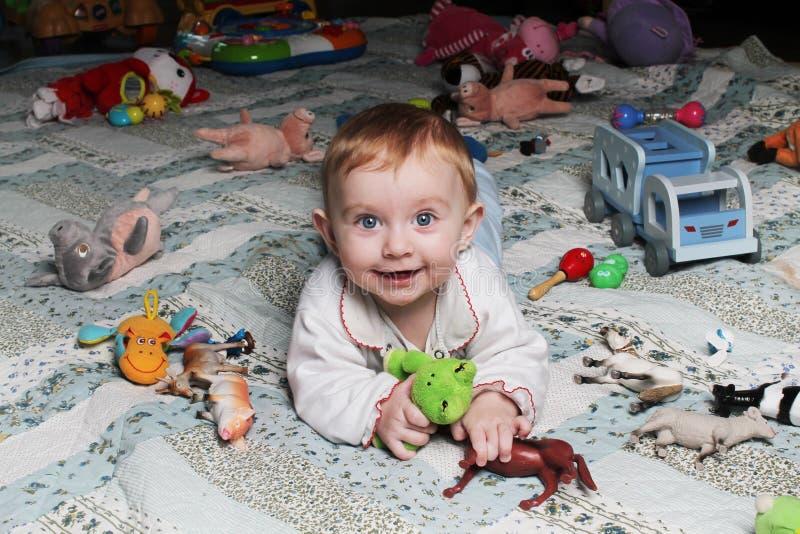 Χαμογελώντας κοριτσάκι στο πάτωμα με τα παιχνίδια στοκ φωτογραφίες με δικαίωμα ελεύθερης χρήσης