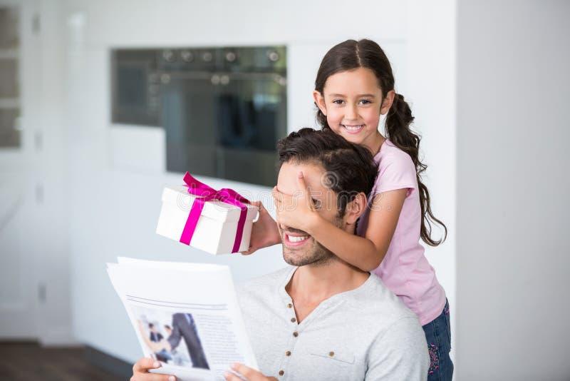 Χαμογελώντας κόρη που καλύπτει τα μάτια πατέρων κρατώντας το κιβώτιο δώρων στοκ φωτογραφία με δικαίωμα ελεύθερης χρήσης