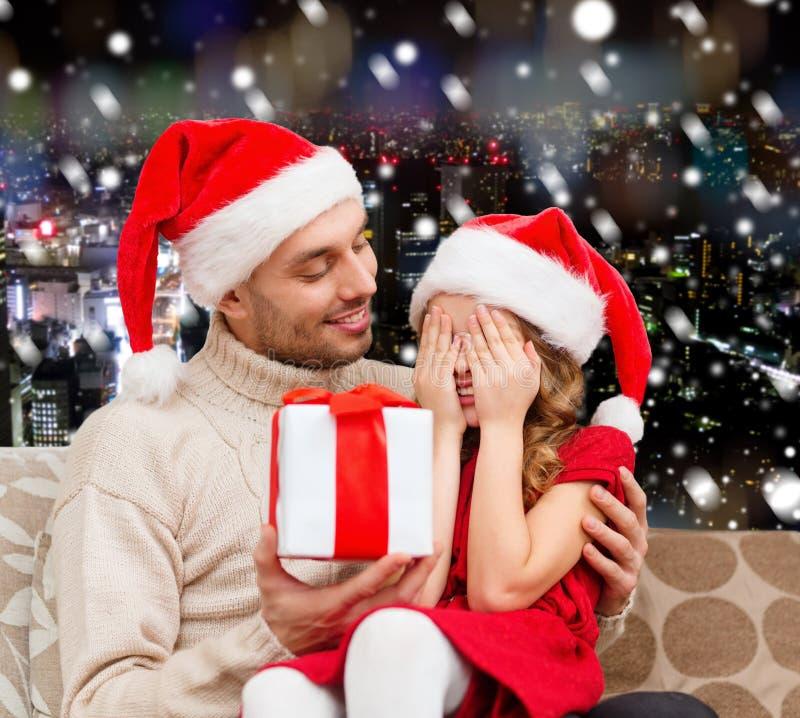 Χαμογελώντας κόρη που περιμένει το παρόν από τον πατέρα στοκ εικόνα