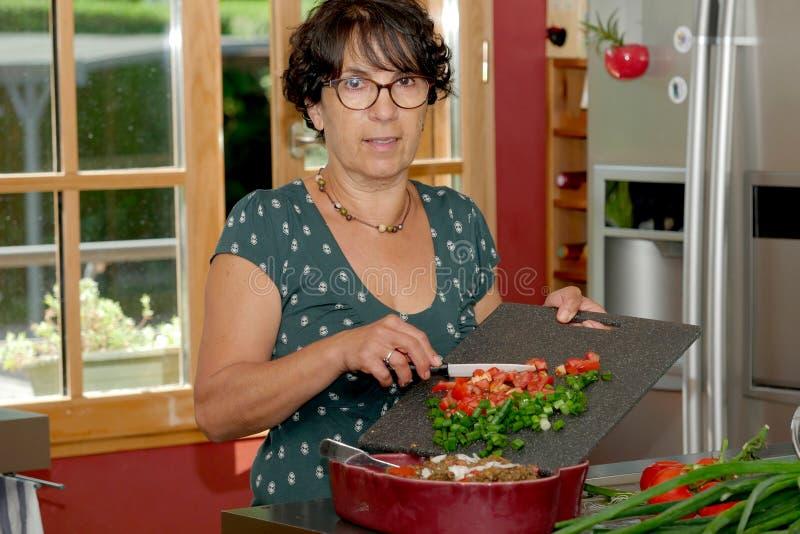 Χαμογελώντας μέσης ηλικίας γυναίκα brunette που προετοιμάζει το γεύμα στοκ εικόνα