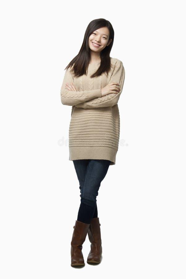 Χαμογελώντας μακρυμάλλης νέα γυναίκα σε ένα πουλόβερ με τα όπλα που διασχίζονται, πορτρέτο, πυροβολισμός στούντιο στοκ εικόνες