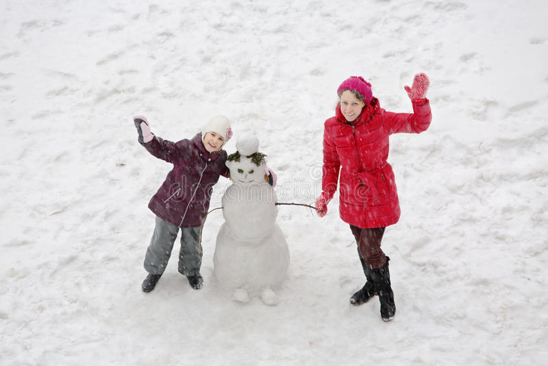 Χαμογελώντας μητέρα και κόρη που στέκονται δίπλα σε έναν χιονάνθρωπο στοκ εικόνες