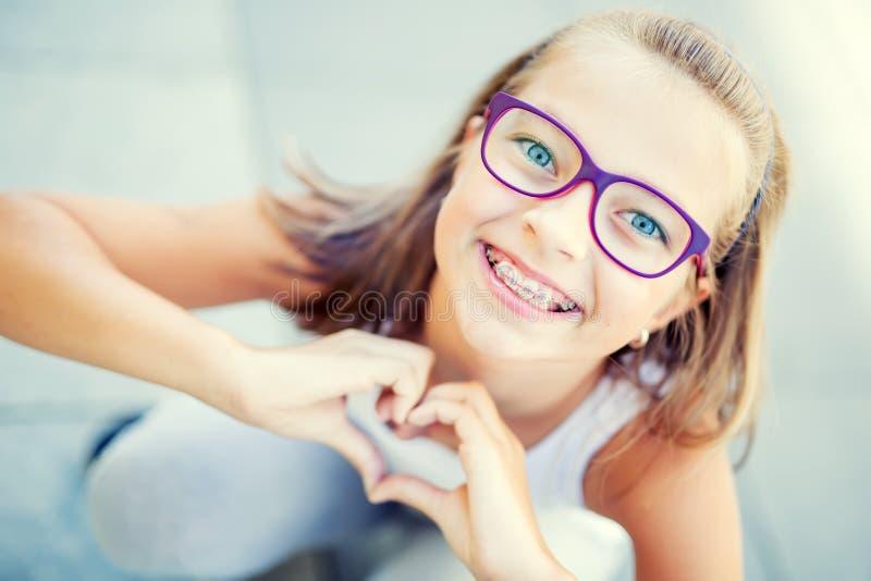 Χαμογελώντας μικρό κορίτσι μέσα με τα στηρίγματα και τα γυαλιά που παρουσιάζουν καρδιά με τα χέρια στοκ εικόνες