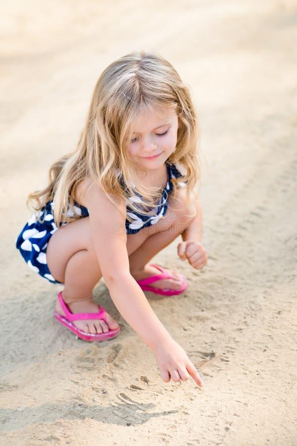 Χαμογελώντας μικρό κορίτσι με τα μακριά ξανθά μαλλιά που κάθονται οκλαδόν και που σύρουν στην άμμο στοκ εικόνες