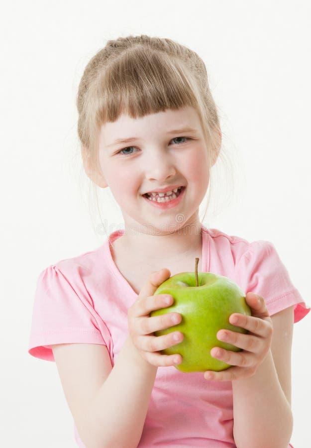 Χαμογελώντας μικρό κορίτσι που κρατά ένα πράσινο μήλο στοκ εικόνα