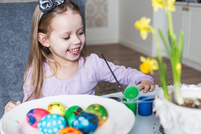 Χαμογελώντας μικρό κορίτσι που χρωματίζει τα αυγά Πάσχας στοκ εικόνες με δικαίωμα ελεύθερης χρήσης