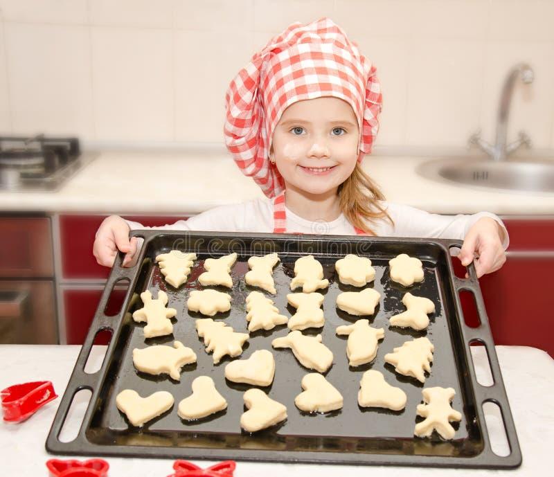 Χαμογελώντας μικρό κορίτσι στο καπέλο αρχιμαγείρων με το φύλλο ψησίματος των μπισκότων στοκ εικόνα με δικαίωμα ελεύθερης χρήσης