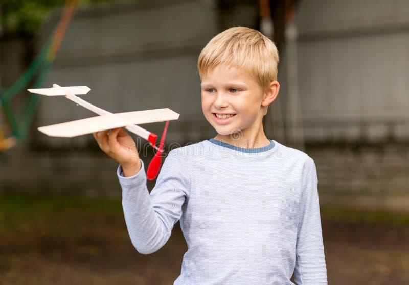 Χαμογελώντας μικρό παιδί που κρατά ένα ξύλινο πρότυπο αεροπλάνων στοκ εικόνα με δικαίωμα ελεύθερης χρήσης