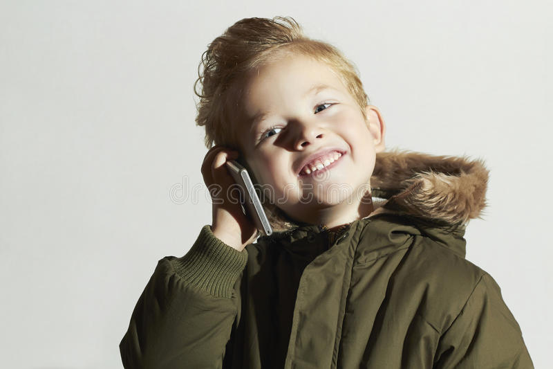 Χαμογελώντας μικρό παιδί που μιλά στο κινητό τηλέφωνο ευτυχές παιδί στο χειμερινό παλτό Παιδιά μόδας Παιδιά στοκ εικόνες