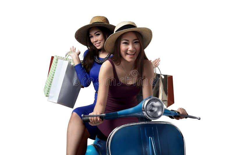 Χαμογελώντας νέα ασιατική γυναίκα δύο που οδηγά το μηχανικό δίκυκλο με τις αγορές β στοκ εικόνα