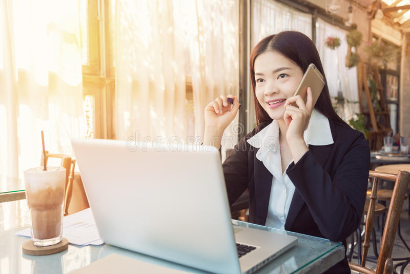 Χαμογελώντας νέα ασιατική εκτελεστική επιχειρησιακή γυναίκα που εργάζεται σε έναν καφέ στοκ φωτογραφία