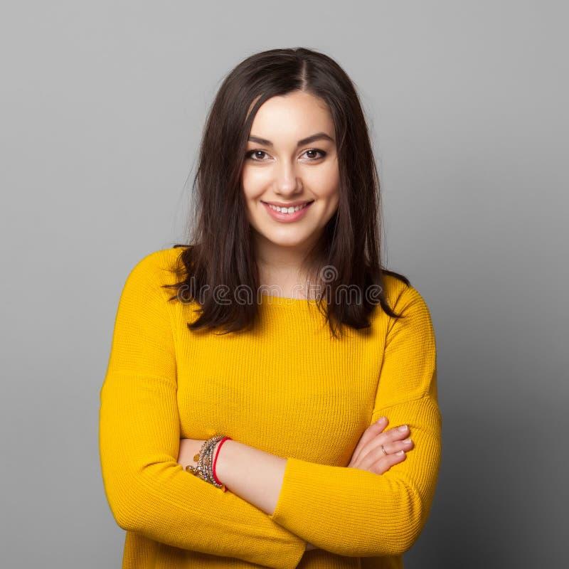 Χαμογελώντας νέα γυναίκα με τα διπλωμένα χέρια στοκ φωτογραφίες με δικαίωμα ελεύθερης χρήσης