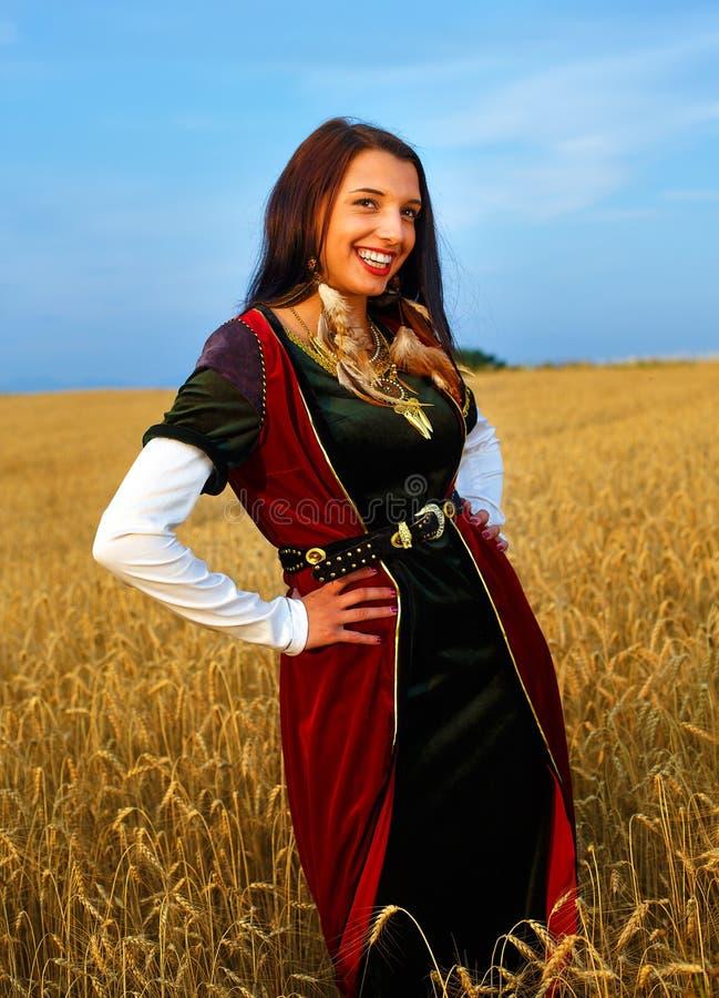 Χαμογελώντας νέα γυναίκα με το μεσαιωνικό φόρεμα που στέκεται σε έναν τομέα σίτου με το ηλιοβασίλεμα Φυσική ανασκόπηση στοκ εικόνα με δικαίωμα ελεύθερης χρήσης