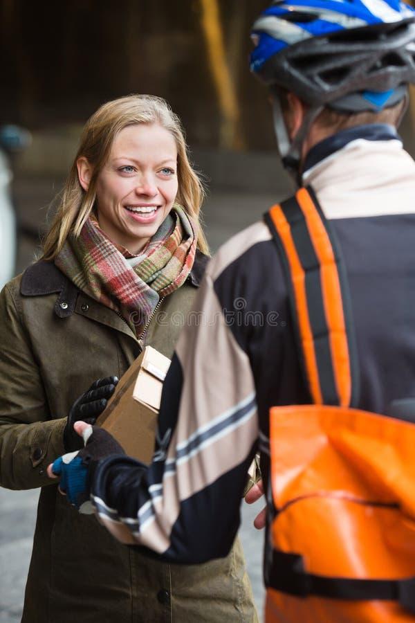 Χαμογελώντας νέα γυναίκα που λαμβάνει μια συσκευασία από στοκ εικόνες