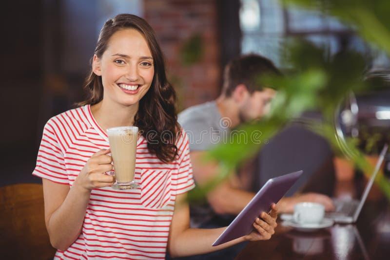 Χαμογελώντας νέα γυναίκα που απολαμβάνουν latte και χρησιμοποίηση του υπολογιστή ταμπλετών στοκ φωτογραφίες με δικαίωμα ελεύθερης χρήσης