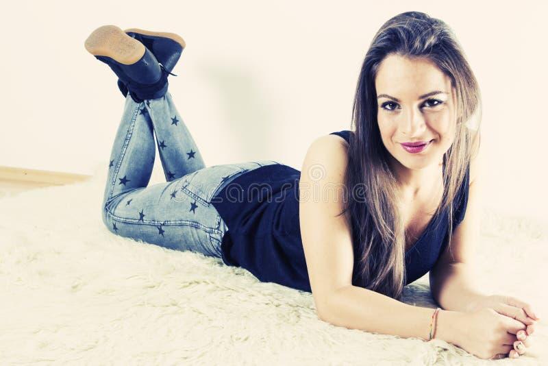 Χαμογελώντας νέα γυναίκα που βάζει στο πάτωμα στοκ εικόνες