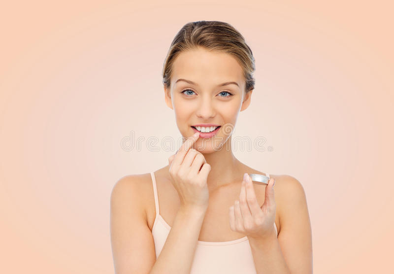 Χαμογελώντας νέα γυναίκα που εφαρμόζει το χειλικό βάλσαμο στα χείλια της στοκ εικόνες