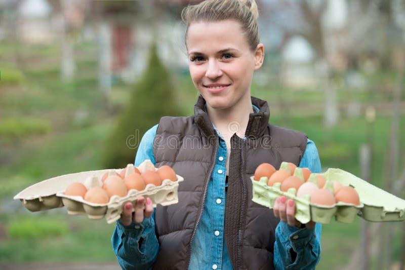 Χαμογελώντας νέα γυναίκα που κρατά τα φρέσκα αυγά κοτόπουλου στα χέρια υπαίθρια στοκ εικόνα με δικαίωμα ελεύθερης χρήσης