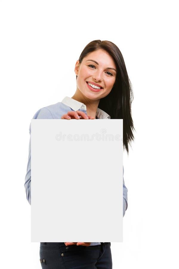 Χαμογελώντας νέα γυναίκα που παρουσιάζει κενή πινακίδα στο άσπρο υπόβαθρο στοκ εικόνα με δικαίωμα ελεύθερης χρήσης