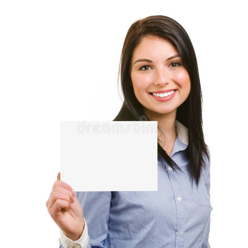 Χαμογελώντας νέα γυναίκα που παρουσιάζει κενή πινακίδα στοκ εικόνες με δικαίωμα ελεύθερης χρήσης