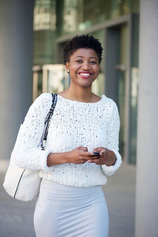 Χαμογελώντας νέα γυναίκα που στέλνει στο μήνυμα κειμένου INT τον πόλη στοκ εικόνες με δικαίωμα ελεύθερης χρήσης