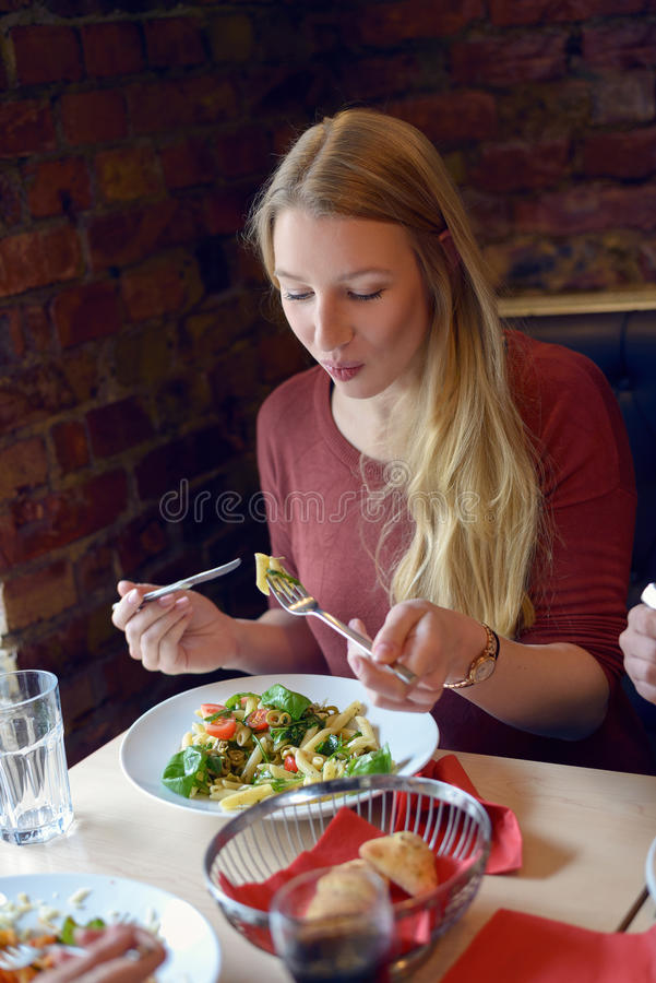 Χαμογελώντας νέα γυναίκα που τρώει μια σαλάτα στο εστιατόριο στοκ εικόνες με δικαίωμα ελεύθερης χρήσης