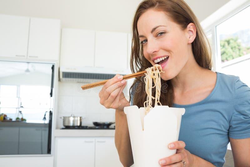 Χαμογελώντας νέα γυναίκα που τρώει τα νουντλς στην κουζίνα στοκ φωτογραφίες με δικαίωμα ελεύθερης χρήσης