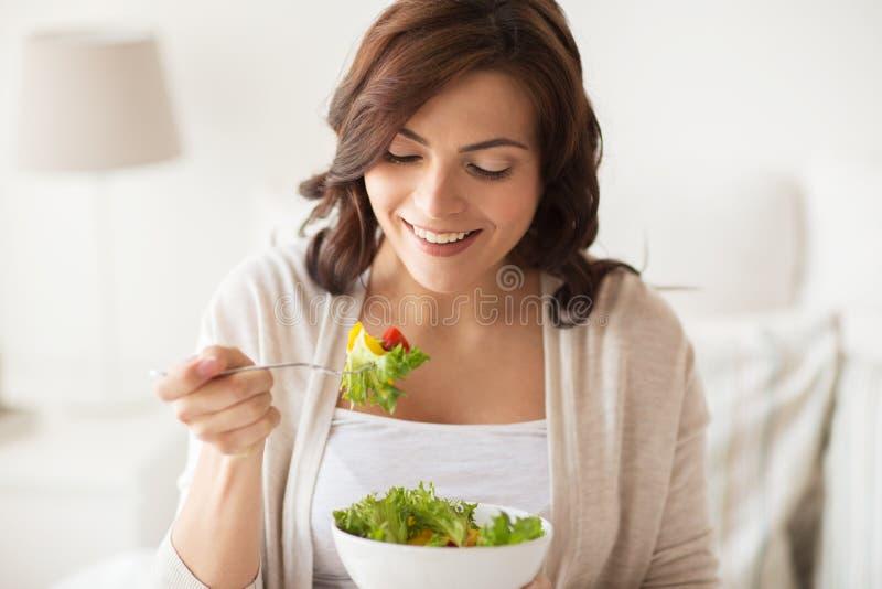 Χαμογελώντας νέα γυναίκα που τρώει τη σαλάτα στο σπίτι στοκ φωτογραφία