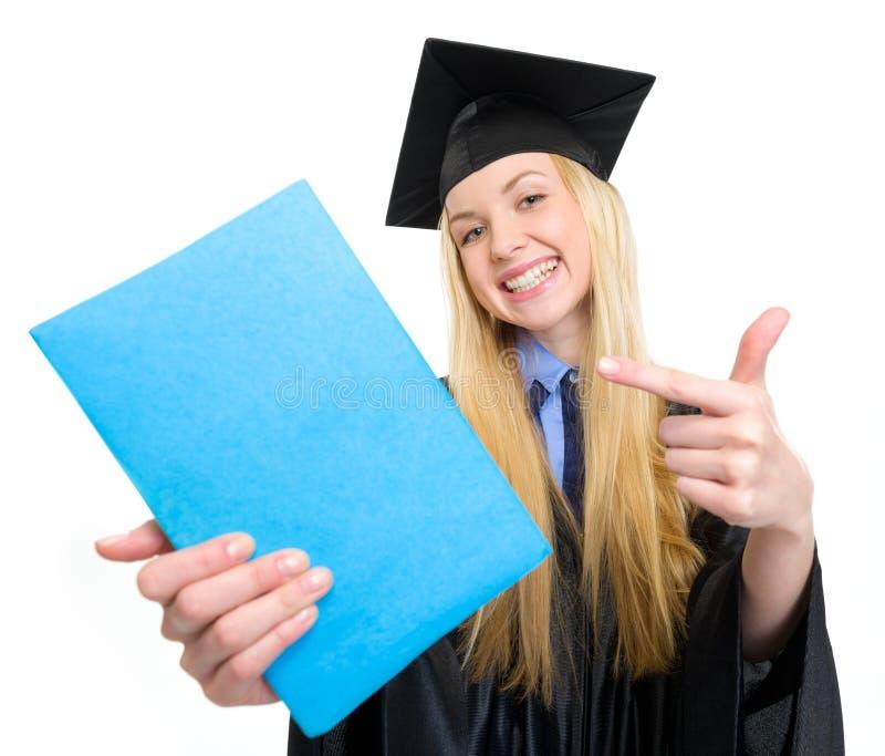 Χαμογελώντας νέα γυναίκα στην εσθήτα βαθμολόγησης που δείχνει στο βιβλίο στοκ εικόνα με δικαίωμα ελεύθερης χρήσης