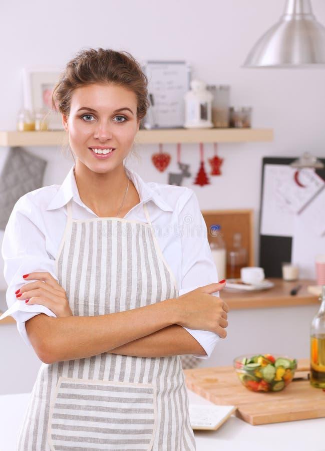 Χαμογελώντας νέα γυναίκα στην κουζίνα στοκ εικόνα