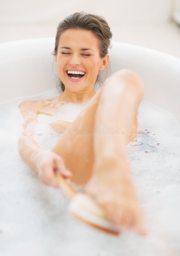 Χαμογελώντας νέα γυναίκα στην μπανιέρα που χρησιμοποιεί τη βούρτσα σωμάτων στοκ φωτογραφία με δικαίωμα ελεύθερης χρήσης