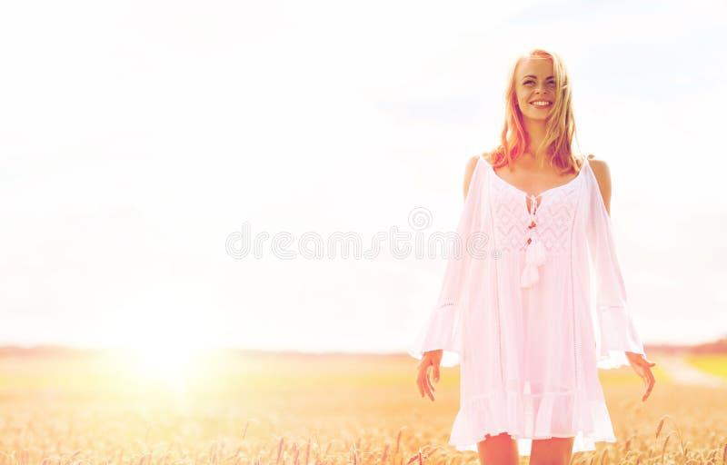 Χαμογελώντας νέα γυναίκα στο άσπρο φόρεμα στον τομέα δημητριακών στοκ εικόνα