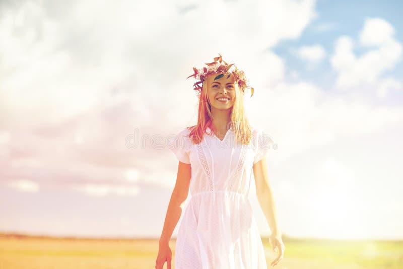 Χαμογελώντας νέα γυναίκα στο στεφάνι των λουλουδιών υπαίθρια στοκ εικόνες