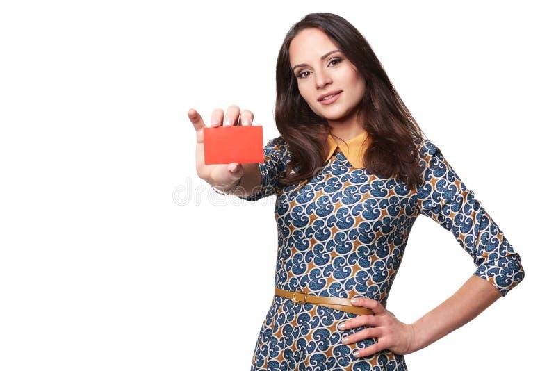 Χαμογελώντας νέα γυναίκα στο φόρεμα colorfull που παρουσιάζει α στοκ φωτογραφία με δικαίωμα ελεύθερης χρήσης