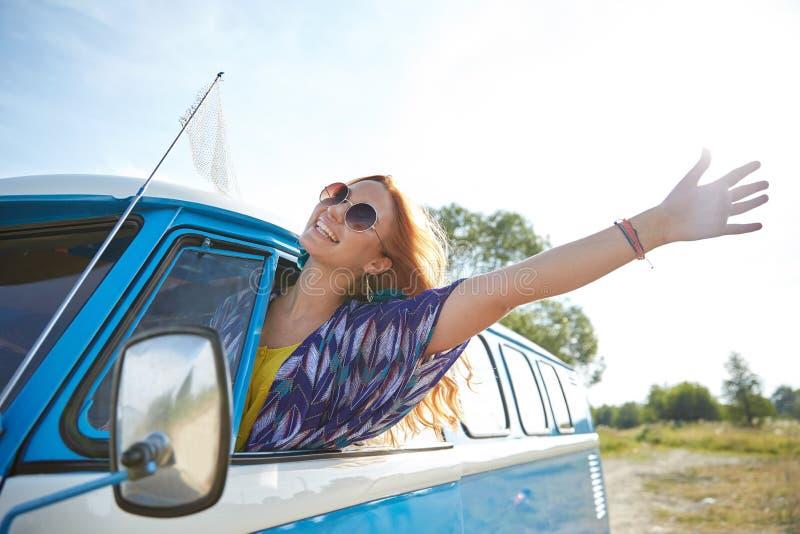 Χαμογελώντας νέα γυναίκα χίπηδων που οδηγεί το minivan αυτοκίνητο στοκ φωτογραφίες