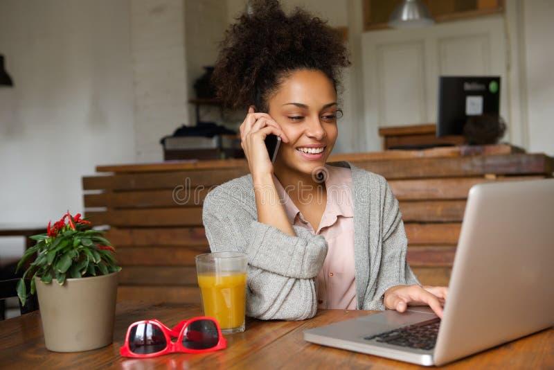 Χαμογελώντας νέα γυναίκα χρησιμοποιώντας το lap-top και μιλώντας στο κινητό τηλέφωνο στοκ φωτογραφία