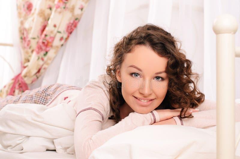 Χαμογελώντας νέα ελκυστική γυναίκα που βρίσκεται στο κρεβάτι στοκ εικόνα με δικαίωμα ελεύθερης χρήσης