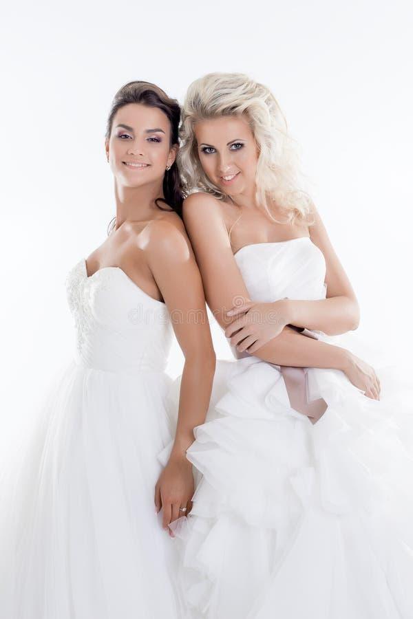 Χαμογελώντας νέα κορίτσια που θέτουν στα γαμήλια φορέματα στοκ φωτογραφία
