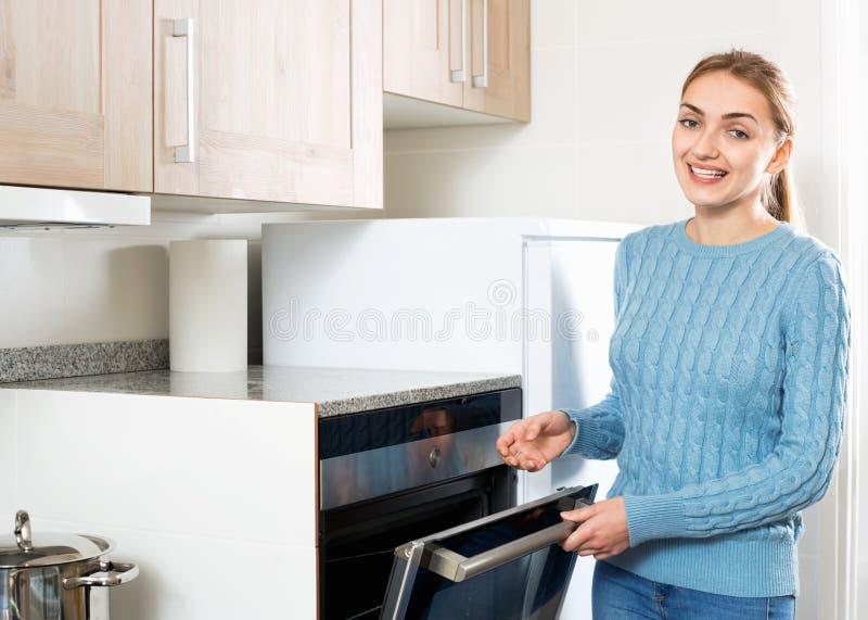 Χαμογελώντας νέα νοικοκυρά που θερμαίνει τον ηλεκτρικό φούρνο στοκ φωτογραφίες με δικαίωμα ελεύθερης χρήσης