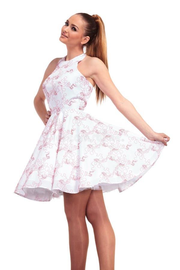 Χαμογελώντας νέα όμορφη γυναίκα που παρουσιάζει φόρεμά της στοκ εικόνα
