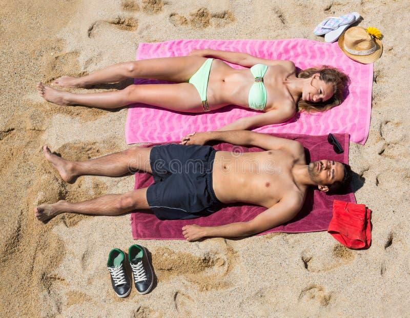 Χαμογελώντας νέοι εραστές που κάνουν ηλιοθεραπεία στην αμμώδη παραλία στοκ φωτογραφίες με δικαίωμα ελεύθερης χρήσης