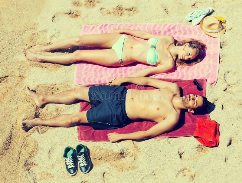 Χαμογελώντας νέοι εραστές που κάνουν ηλιοθεραπεία στην αμμώδη παραλία στοκ φωτογραφία