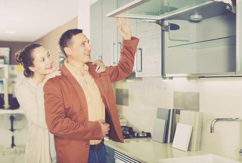Χαμογελώντας νέοι πελάτες που επιλέγουν τη νέα κουζίνα στοκ εικόνες με δικαίωμα ελεύθερης χρήσης
